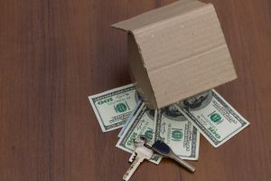 Small cardboard house, keys and dollars on wooden table